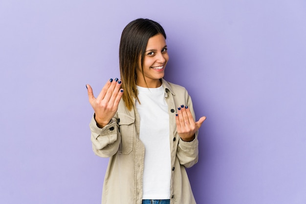 誘うようにあなたに指で指している紫色に孤立した若い女性が近づいています。