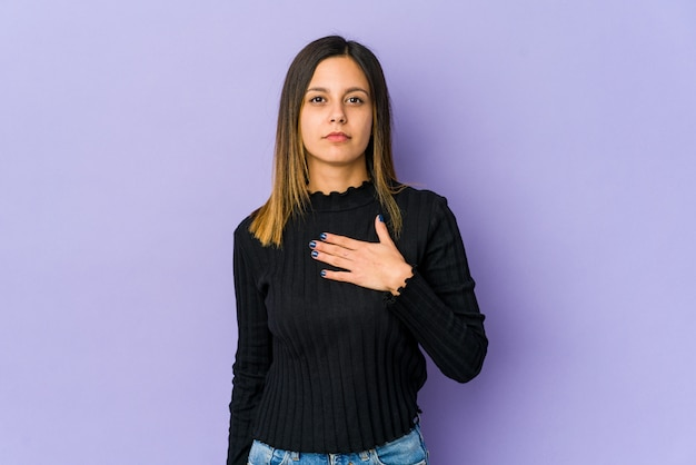 Молодая женщина изолированная на пурпуре принимая присягу, кладя руку на комод.