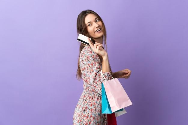 ショッピングバッグとクレジットカードを保持している紫色の壁に孤立した若い女性