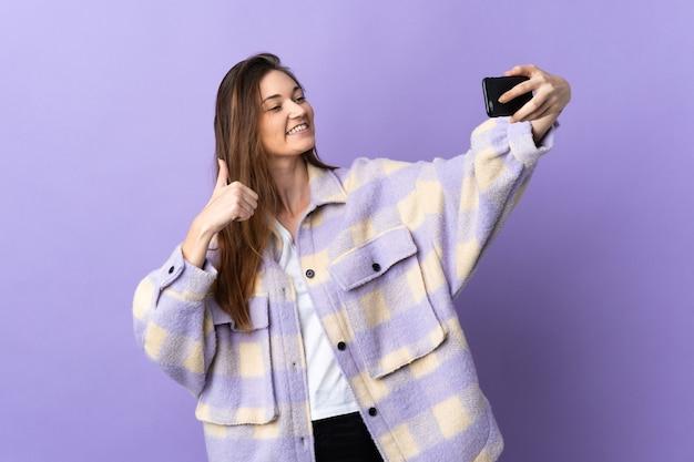 携帯電話でselfieを作る紫色の壁に孤立した若い女性