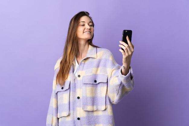 Молодая женщина изолирована на фиолетовой стене, делая селфи с мобильным телефоном