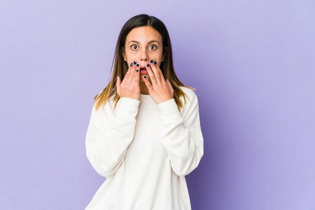 Молодая женщина, изолированная на фиолетовой стене потрясена прикрытием рта руками.