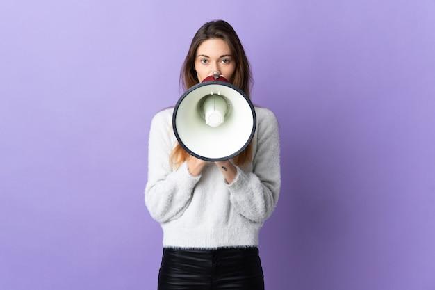 뭔가를 발표하기 위해 확성기를 통해 외치는 보라색 벽에 고립 된 젊은 여자