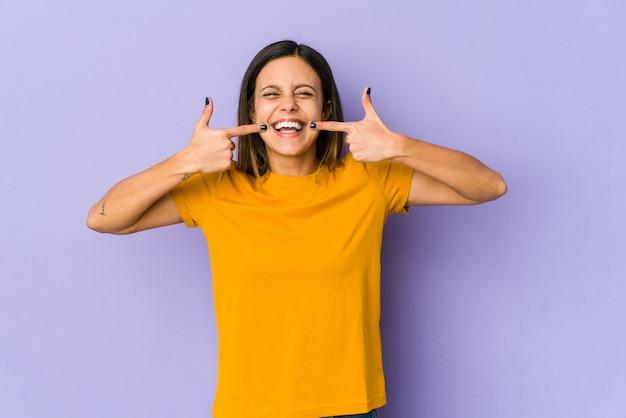 입에 손가락을 가리키는 보라색 벽 미소에 고립 된 젊은 여자.