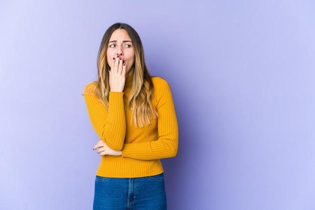 手で口を覆う疲れたジェスチャーを示すあくびをする紫色の壁に孤立した若い女性