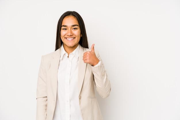Молодая женщина, изолированная на белом, улыбается и поднимает палец вверх