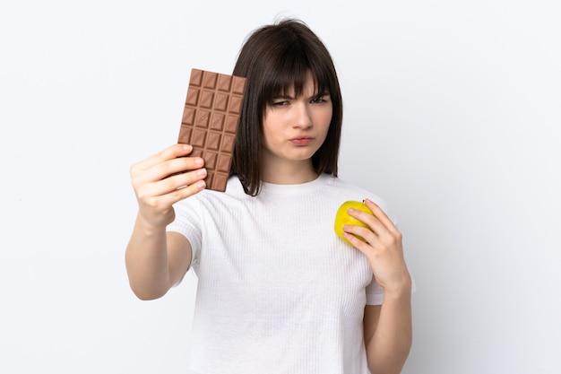 Молодая женщина изолирована на белом, принимая шоколадную таблетку в одной руке и яблоко в другой