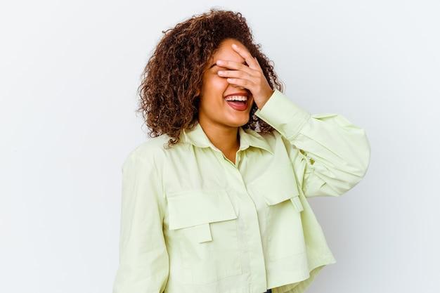 흰 벽에 고립 된 젊은 여자는 손으로 눈을 덮고 미소는 놀라움을 광범위하게 기다리고 있습니다.