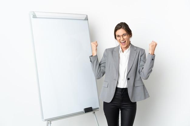 화이트 보드에 프레젠테이션을하고 승리를 축하 흰 벽에 고립 된 젊은 여자