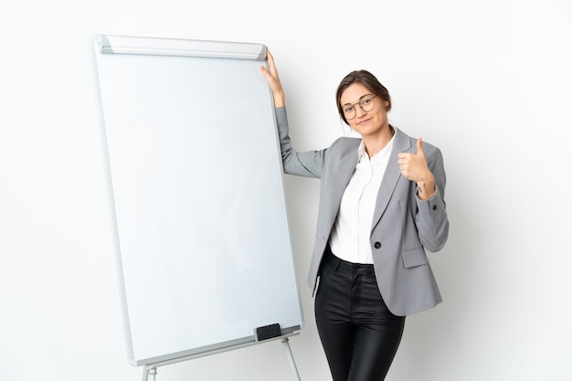 엄지 손가락으로 화이트 보드에 프레 젠 테이 션을주는 흰 벽에 고립 된 젊은 여자