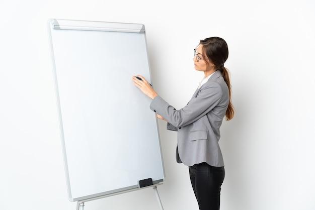 화이트 보드에 프레젠테이션을 흰 벽에 고립 된 젊은 여자
