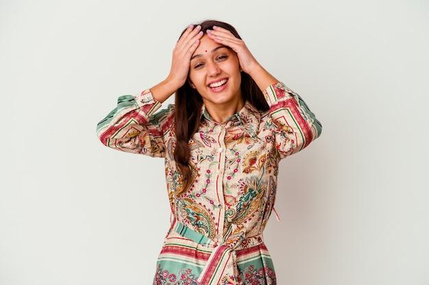 白い壁に隔離された若い女性は頭に手を置いて喜んで笑う