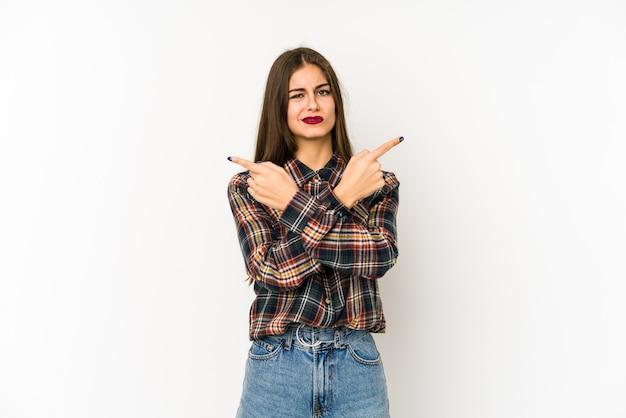 Молодая женщина, изолированная на белой стене указывает боком, пытается выбрать один из двух вариантов