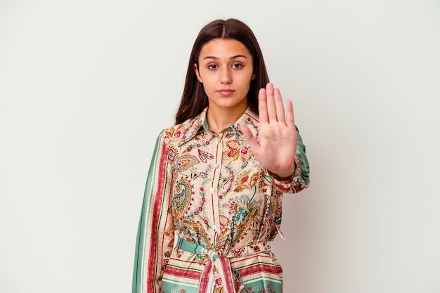 一時停止の標識を示して、あなたを防ぐために伸ばした手で立っている白い壁に孤立した若い女性