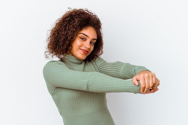 Молодая женщина изолирована на белой стене, протягивая руки, расслабленное положение