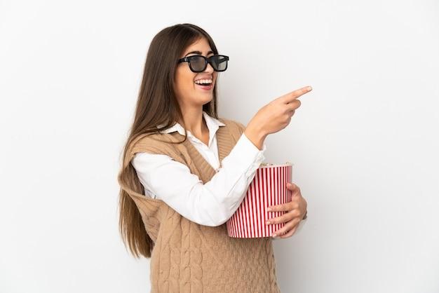 3dメガネで白い壁に隔離され、離れて指している間ポップコーンの大きなバケツを保持している若い女性