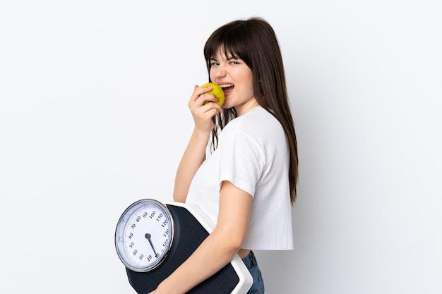 무게 기계와 사과와 흰색에 고립 된 젊은 여자