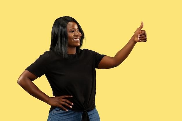 Молодая женщина, изолированные на желтой стене студии