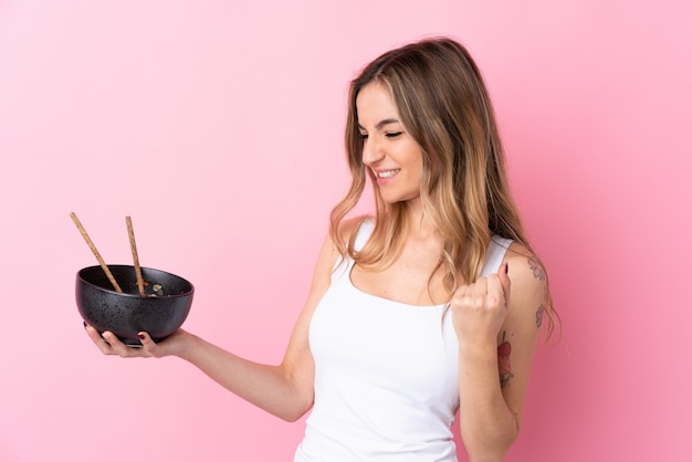 Young woman over isolated pink wall celebrating a victory while holding a bowl of noodles with chopsticks