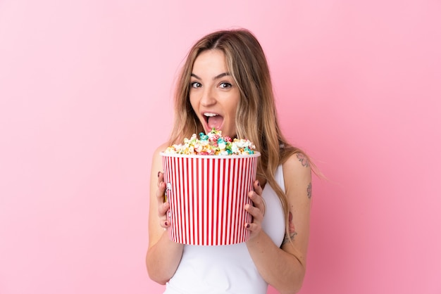 Young woman over isolated pink wall holding a big bucket of popcorns