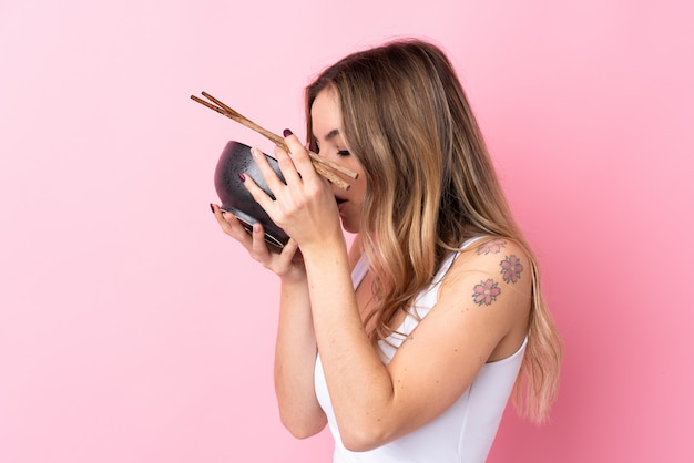 Young woman over isolated pink wall holding a bowl of noodles with chopsticks and eating it