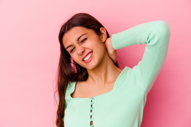 Young woman isolated on pink wall suffering neck pain due to sedentary lifestyle