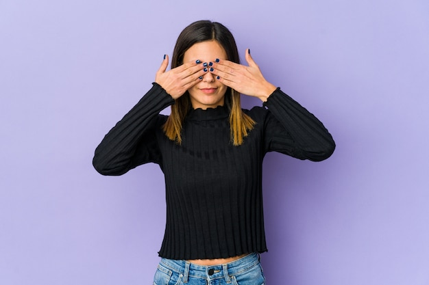 Young woman isolated on purple wall afraid covering eyes with hands.