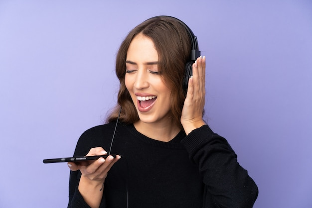 Young woman over isolated purple wall listening music with a mobile and singing