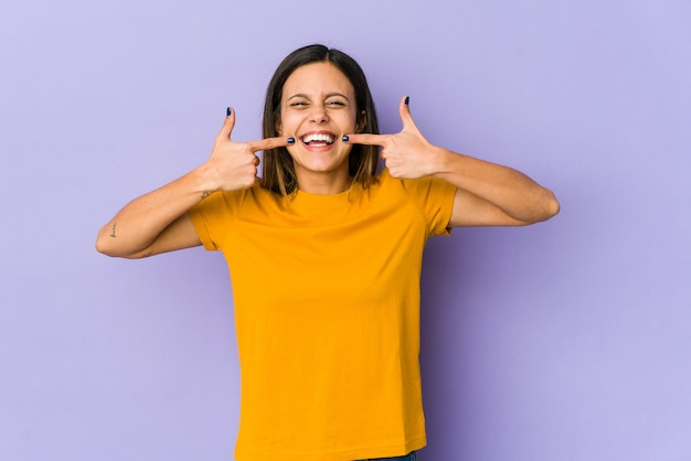 Young woman isolated on purple wall smiles, pointing fingers at mouth.