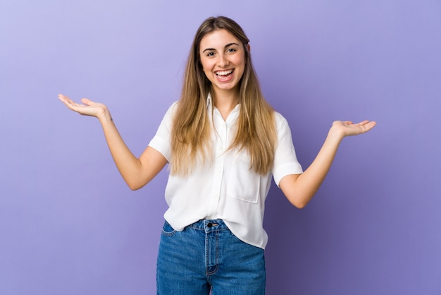 Young woman over isolated purple wall with shocked facial expression