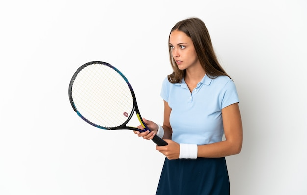 Young woman over isolated white background playing tennis