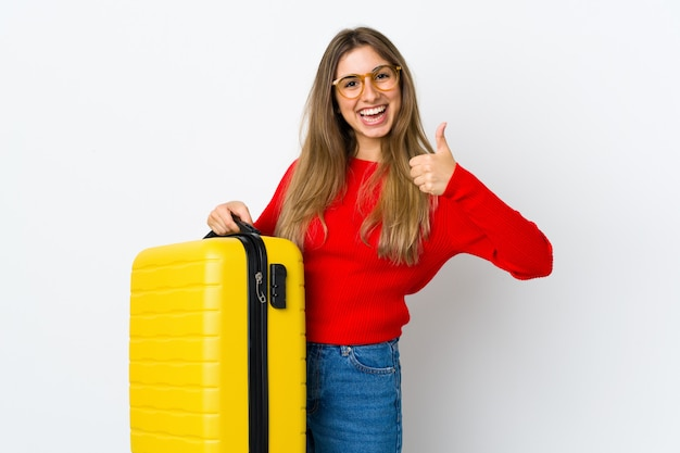 Young woman on isolated white in vacation with travel suitcase and with thumb up