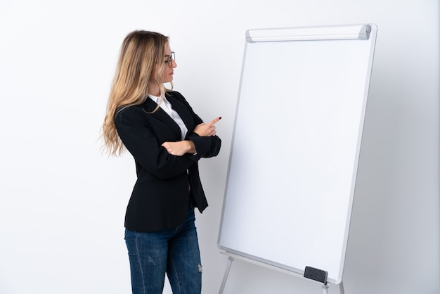 Young woman over isolated white wall giving a presentation on white board and pointing it