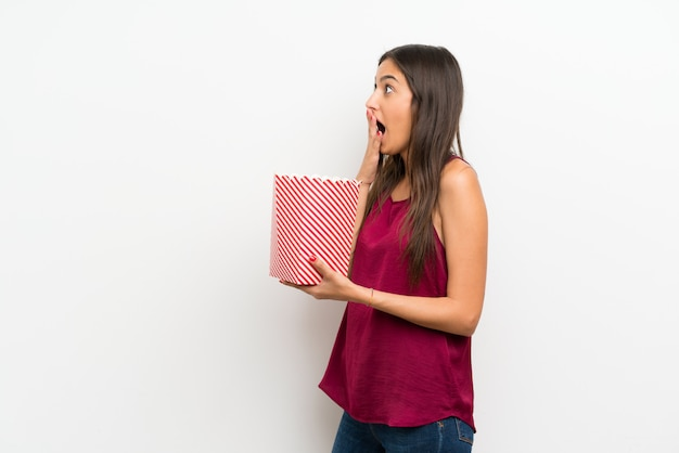 Young woman over isolated white wall holding a bowl of popcorns