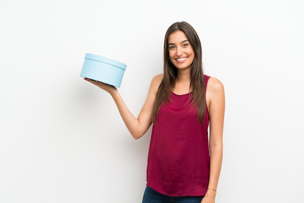 Young woman over isolated white wall holding gift box