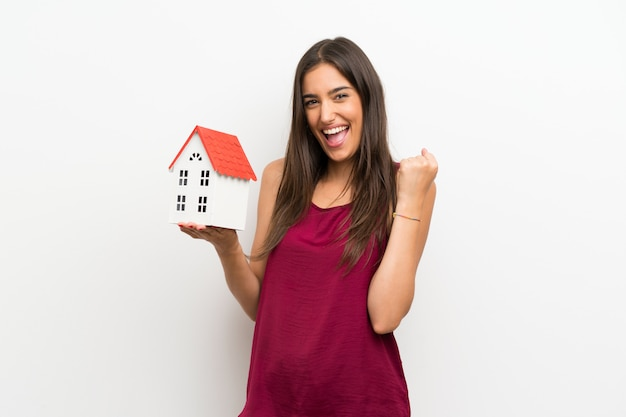 Young woman over isolated white wall holding a little house
