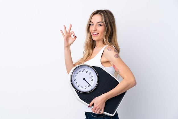 Young woman over isolated white wall holding a weighing machine and doing ok sign