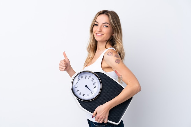 Young woman over isolated white wall holding weighing machine with thumb up