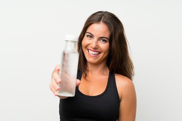 Young woman over isolated white wall with a bottle of water