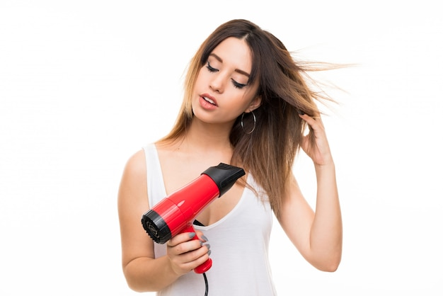 Young woman over isolated white wall with hairdryer