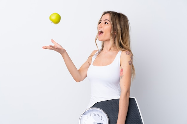 Young woman over isolated white wall with weighing machine and with an apple