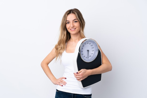 Young woman over isolated white wall with weighing machine