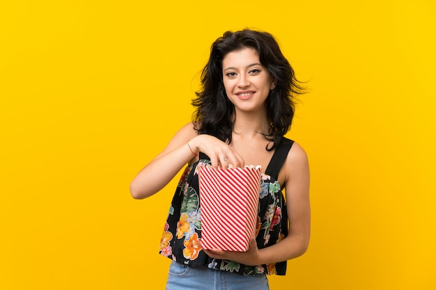 Young woman over isolated yellow background holding a bowl of popcorns