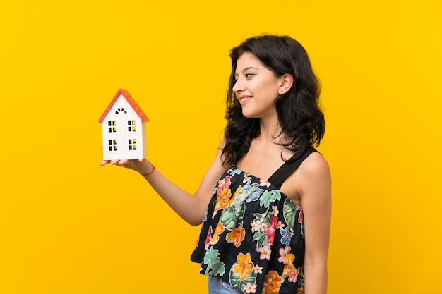 Young woman over isolated yellow background holding a little house