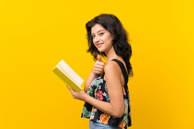 Young woman over isolated yellow background holding and reading a book