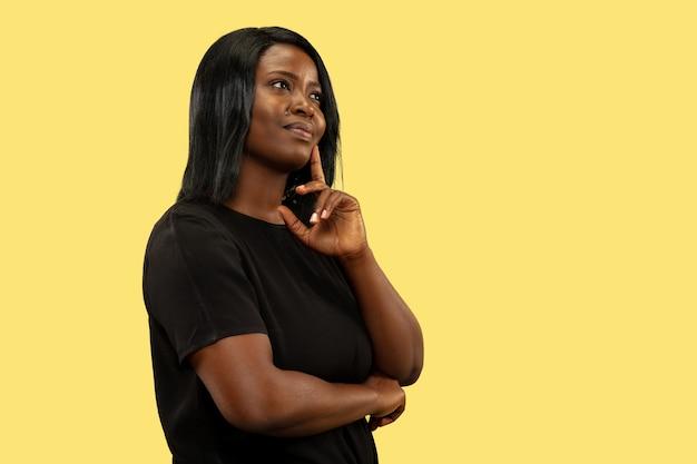 Young woman isolated on yellow studio wall