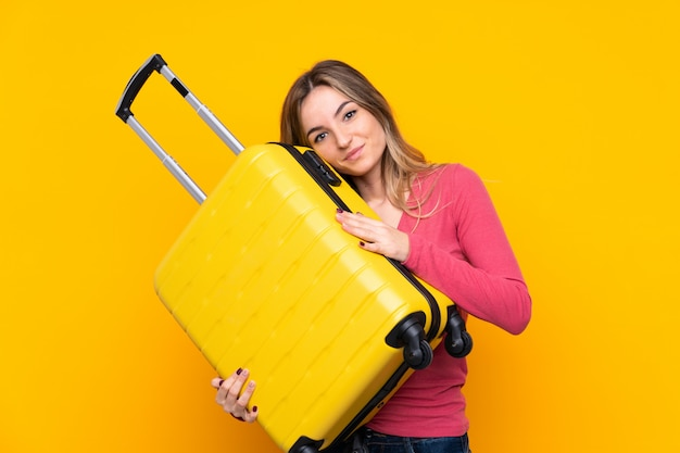 Young woman over isolated yellow wall in vacation with travel suitcase