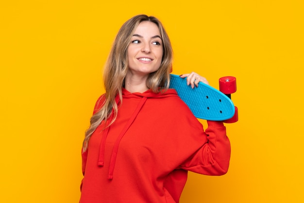 Young woman over isolated yellow wall with a skate with happy expression