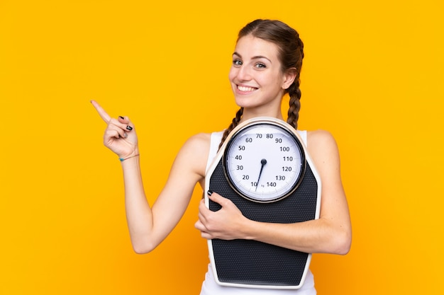 Young woman over isolated yellow wall with weighing machine and pointing side