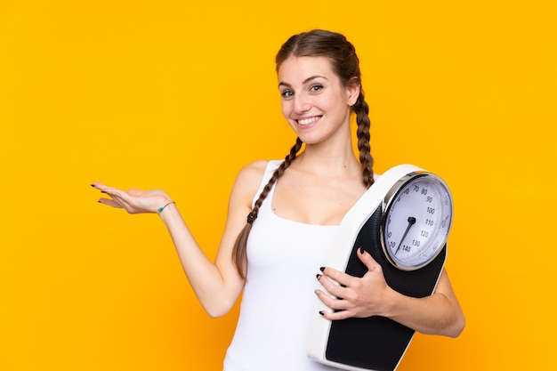 Young woman over isolated yellow wall with weighing machine